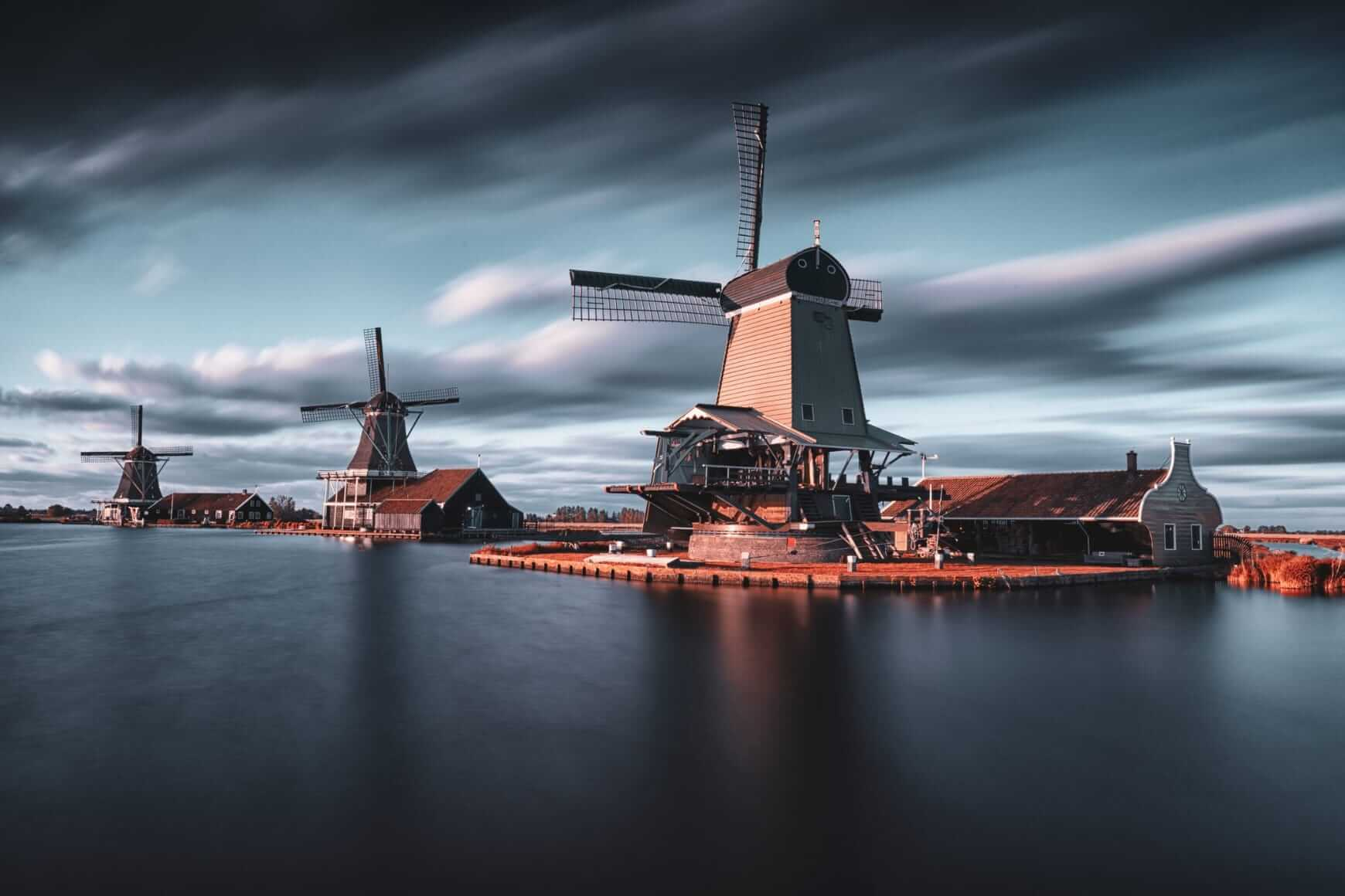 Three windmills next to water with dark sky
