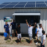 Group of people standing in front of shipping container with solar panels on the roof