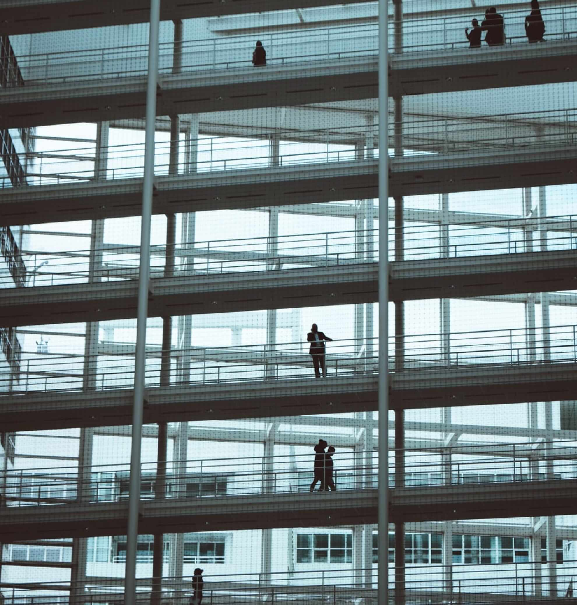 People standing on different floors in building