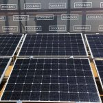 Solar panels lying in front of banner saying Coolback