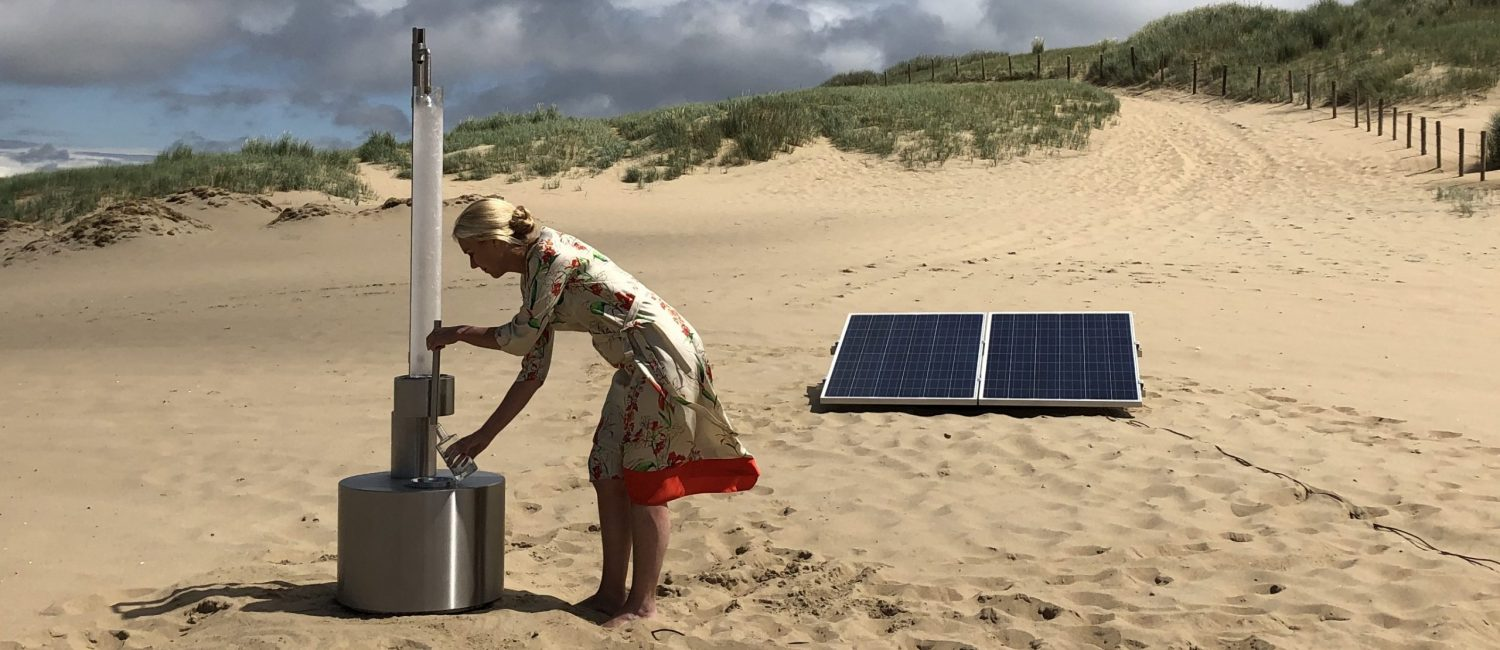 Sigrid Kaag standing by tap in sand with solar panel behind it