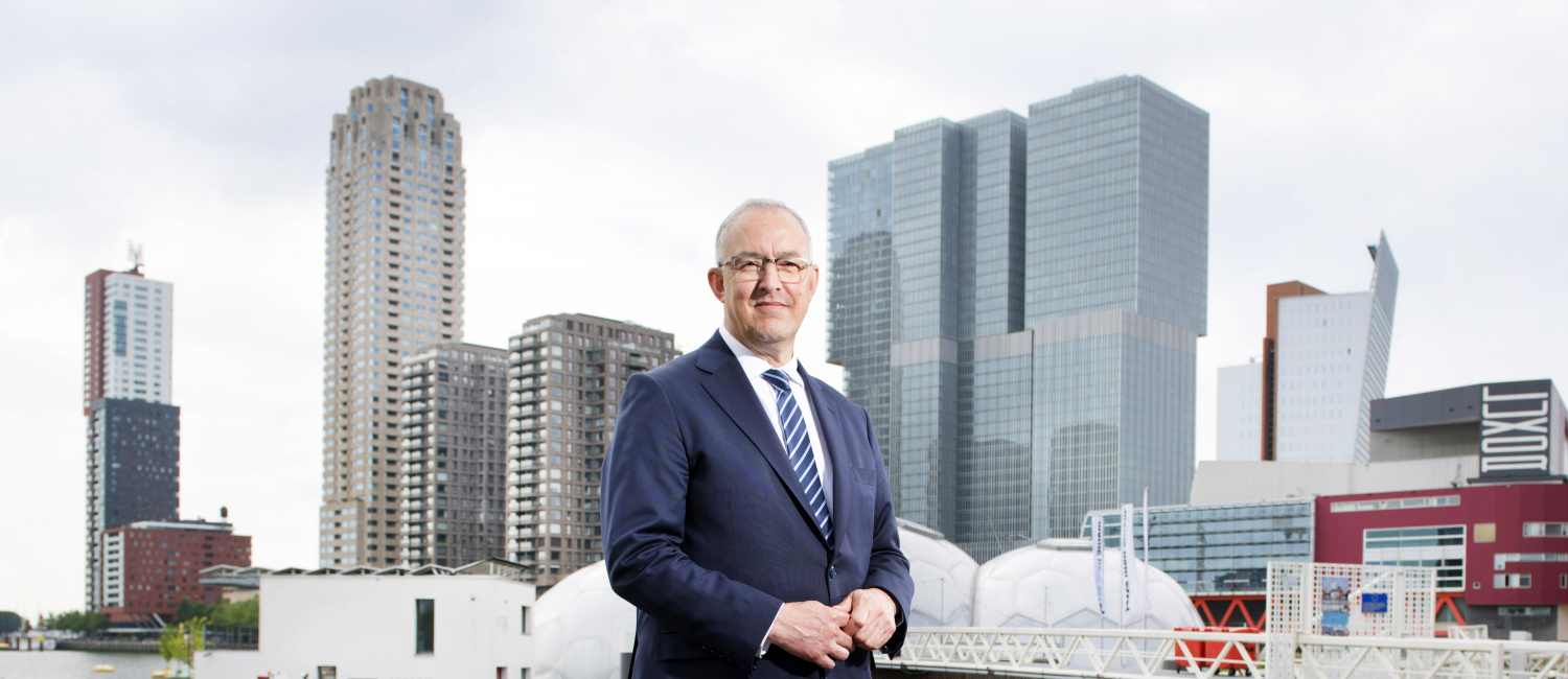 Ahmed Aboutaleb in dark blue suit standing in front of skyline Rotterdam