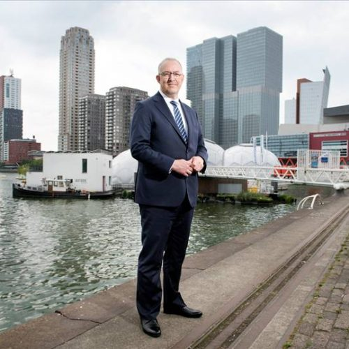 Portrait photo of Mayor Aboutaleb in front of Rotterdam skyline