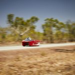 Red solar car driving on road